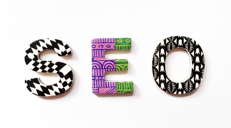Le tre lettere che compongono la parola SEO, appoggiate su uno sfondo bianco